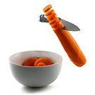 Knife chopping carrot slices into white bowl by Gert Lavsen