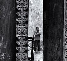 African boy in courtyard Stone Town by Amyn Nasser