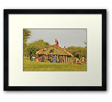 Masai women building a home in Tanzania Framed Print