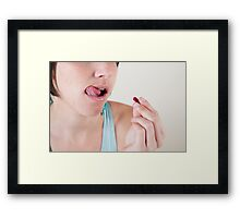Female model in her 20s swallowing a vitamin pill Framed Print