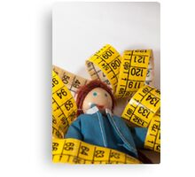 Doll resting on measuring tape Canvas Print
