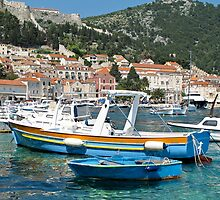 blue boats in harbour at Hvar by Anne Scantlebury