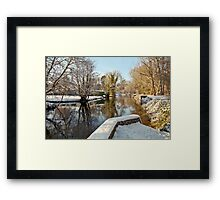 Snow on the river-bank Framed Print