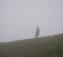 Man walking on hillside in fog by Michael Brewer