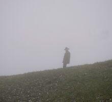 Man walking on hillside in fog by Michael Brewer