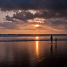 Two figures looking into the sunset under dark clouds at Seminyak Beach in Bali, Indonesia by Michael Brewer