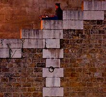 woman sitting on stone steps along the seine river paris by Michael Brewer