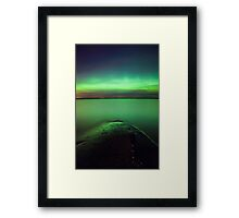 Northern lights glow over lake Framed Print