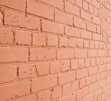 Angle view of a brick wall with a layer of red paint by vladromensky