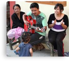 A musician entertaining his family. Canvas Print