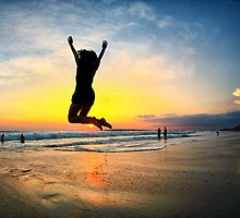 Woman jumping with joy on beach at sunset in Costa Rica by ieatstars