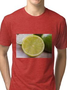 Lime cut as detail on wooden board Tri-blend T-Shirt