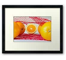 Oranges on a wooden table in the network Framed Print