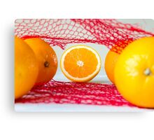 Oranges on a wooden table in the network Canvas Print