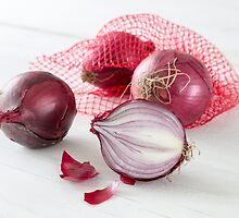 Shallots in the net on white wooden table by wsfbubble