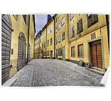 Cobblestone street with yellow houses. Poster