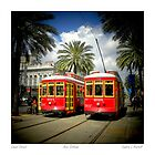 Red Trolly Cars On Canal Street by Sandra Russell