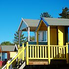 Colourful beach huts against blue sky by Magdalena Warmuz-Dent