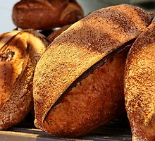 Freshly baked loaves of bread at a bakery by PhotoStock-Isra