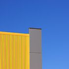 Yellow building on blue sky by Duncan Cunningham
