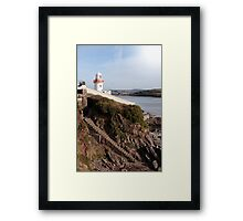 lighthouse with steps down to rocky beach during a sunny day Framed Print