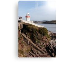 lighthouse with steps down to rocky beach during a sunny day Canvas Print