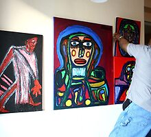 The artist Darrell Black in his studio hanging paintings by definism