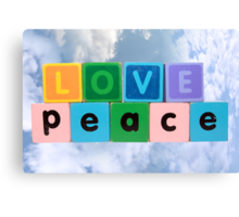 love on peace in wood play block letters against clouds Canvas Print