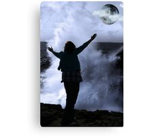 one woman with raised hands facing a wave and full moon on cliff edge Canvas Print