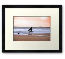 silhouette of a horse and rider galloping along shore Framed Print