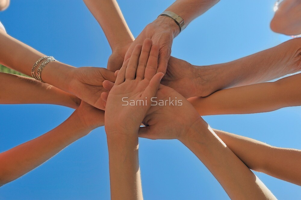 Six people stacking their hands on blue sky by Sami Sarkis