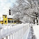 Yellow House with Snow Covered Picket Fence by Susan Savad