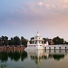 Pond and temple at sunset by Om Yadav