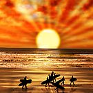 surfers walking on sunset beach by morrbyte