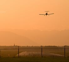Light airplane landing at sunset on the summer solstice by Ian Middleton