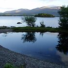 Killarney, reflection in calm blue lake. by Grace Johnson