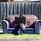 A Lady with a Book on a Couch on a Street on a Hot Day by handyandypandy