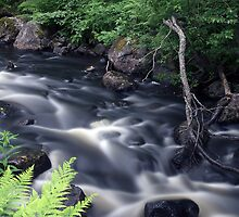 Flowing river by Tommi Rautio