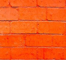 Red background of bricks with a layer of paint close-up by vladromensky