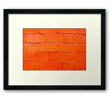 Red background of bricks with a layer of paint close-up Framed Print