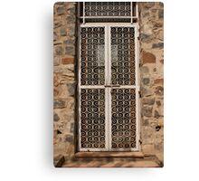 Metal door and stone building Canvas Print