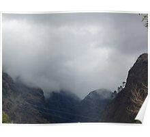 Clouds covering the tops of various mountain peaks Poster