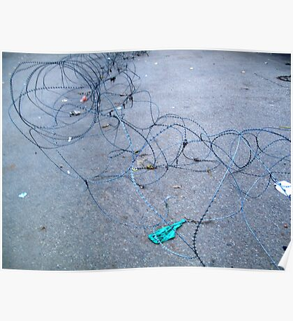 Concertina wire along the ground barring entry to a location Poster