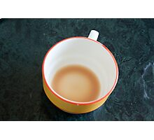 A cup with the remains of tea on a green table Photographic Print