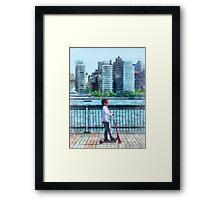 Little Girl on Scooter by Manhattan Skyline Framed Print