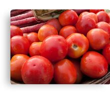 Pile of red luscious tomatoes along with carrots on a vegetable basket Canvas Print