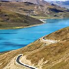 Winding mountain road by bright blue lake by ieatstars