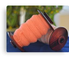 Spinning wheel bobbins orange yarn Canvas Print