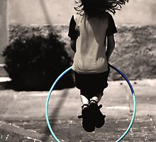 a little girl play with hula hoop by Davide Colombo