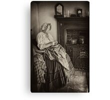 Darning by the fire Canvas Print
